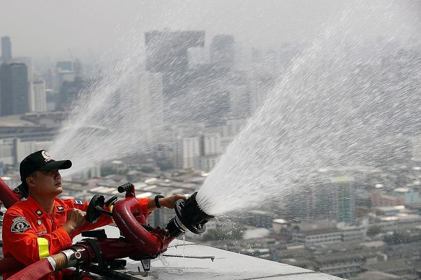 Water being sprayed in the air from the top of a building in the hope of lowering levels of harmful PM2.5 dust particles in Bangkok. Roads are also being regularly hosed down for the same purpose.