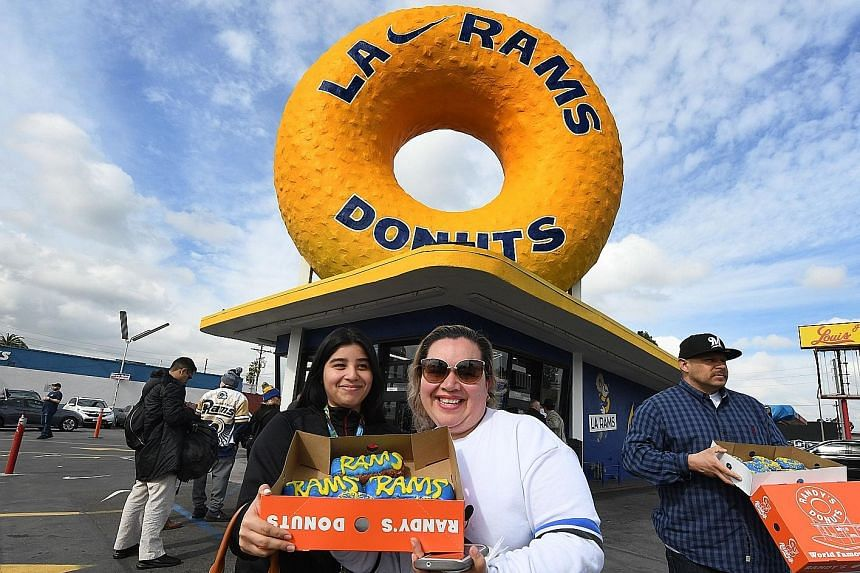 LA Rams fans Katelyn (left) and Nancy Delgado show their team-themed donuts on Friday, ahead of today's Super Bowl final.