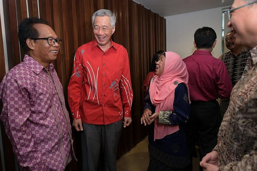 Prime Minister Lee Hsien Loong with Madam Hajjah Hasnah Masnod and her husband, Mr Haji Mawi Ismail, and Health Minister Gan Kim Yong (at right) prior to a tribute event to the Merdeka Generation at Gardens by the Bay yesterday.