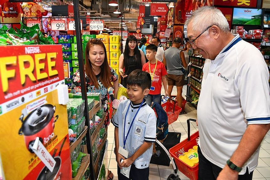 FairPrice chairman Bobby Chin shopping with Cayden Chong, 10, a beneficiary of The Straits Times School Pocket Money Fund, and Cayden's mother, Madam Angelia Chia, 28, at FairPrice Xtra @ Ang Mo Kio Hub on Thursday. FairPrice donated $38,000 to the f
