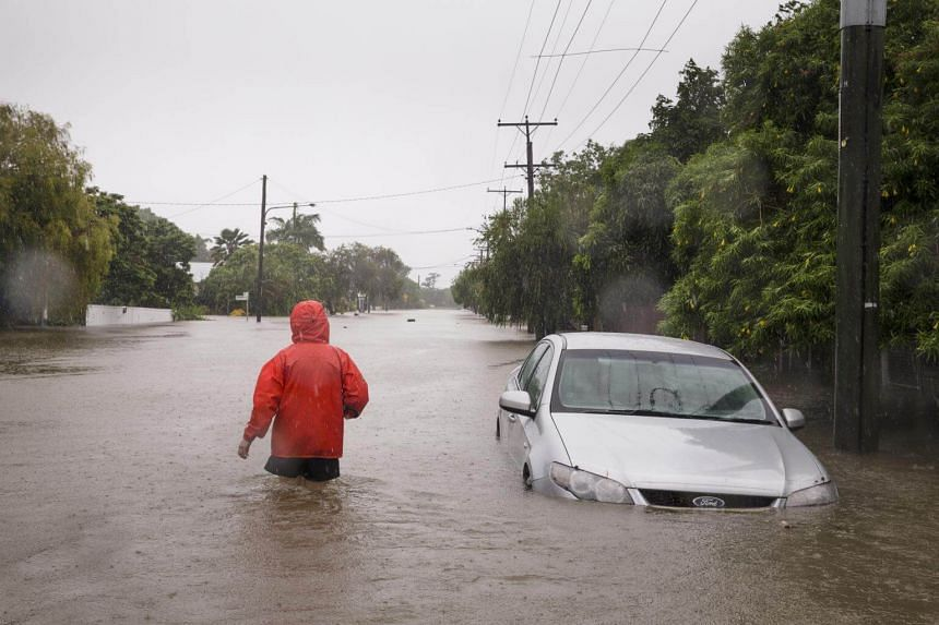 A man walks through flooded area in Townsville, Queensland, on Feb 2, 2019. Thousands of residents in the city were without power and up to 20,000 homes are at risk of being inundated if the rains continue.