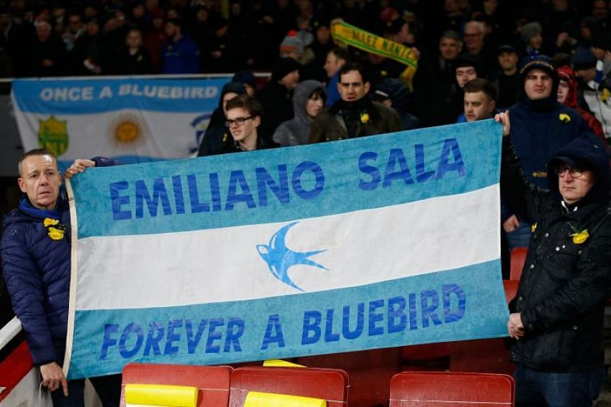 Fans hold up a banner in the colours of the Argentina flag honouring Cardiff's missing Argentinian player Emiliano Sala ahead of the English Premier League football match between Arsenal and Cardiff City at the Emirates Stadium in London, on Jan 29,