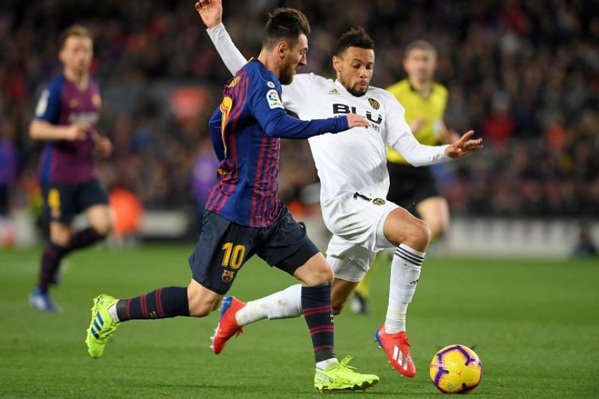 Barcelona's Argentinian forward Lionel Messi (left) vies for the ball with Valencia's French midfielder Francis Coquelin during the Spanish league football match FC Barcelona against Valencia CF at the Camp Nou stadium in Barcelona on Feb 2, 2019.