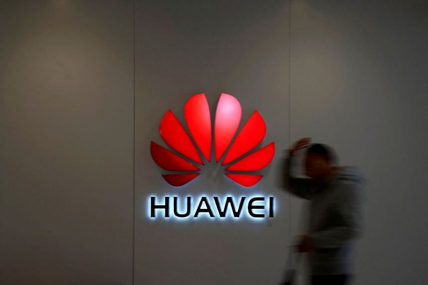 A man walks by a Huawei logo at a shopping mall in Shanghai, China.