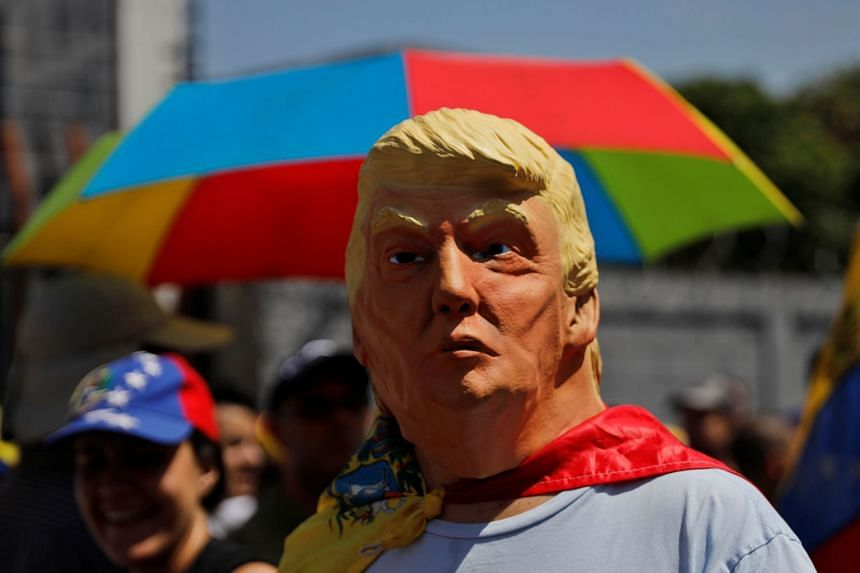 A man wearing a Donald Trump mask attends a rally against Venezuelan President Nicolas Maduro's government in Caracas.
