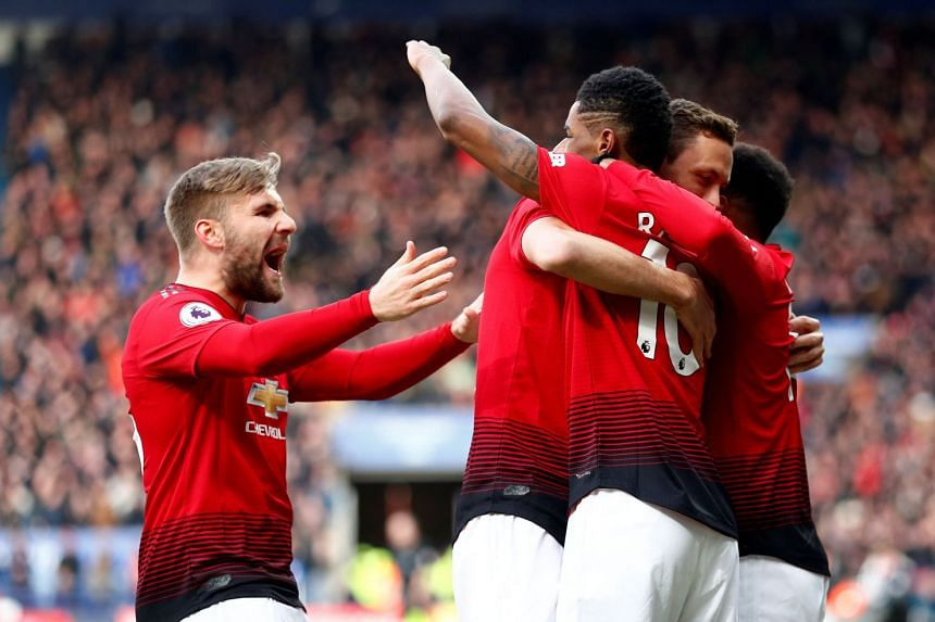 Manchester United's Marcus Rashford celebrates his goal with Luke Shaw and team mates.