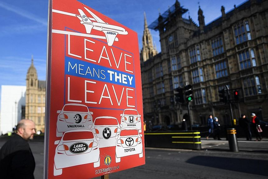 An EU campaign placard outside the Houses of Parliament in London warning that leaving EU would lead to an exit of the car industry and Airbus from Britain.