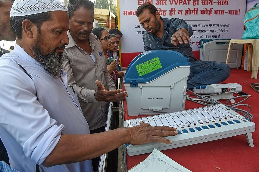 People trying out an electronic voting machine with a voter-verifiable paper audit trail at a demonstration by the Election Commission of India in Mumbai.