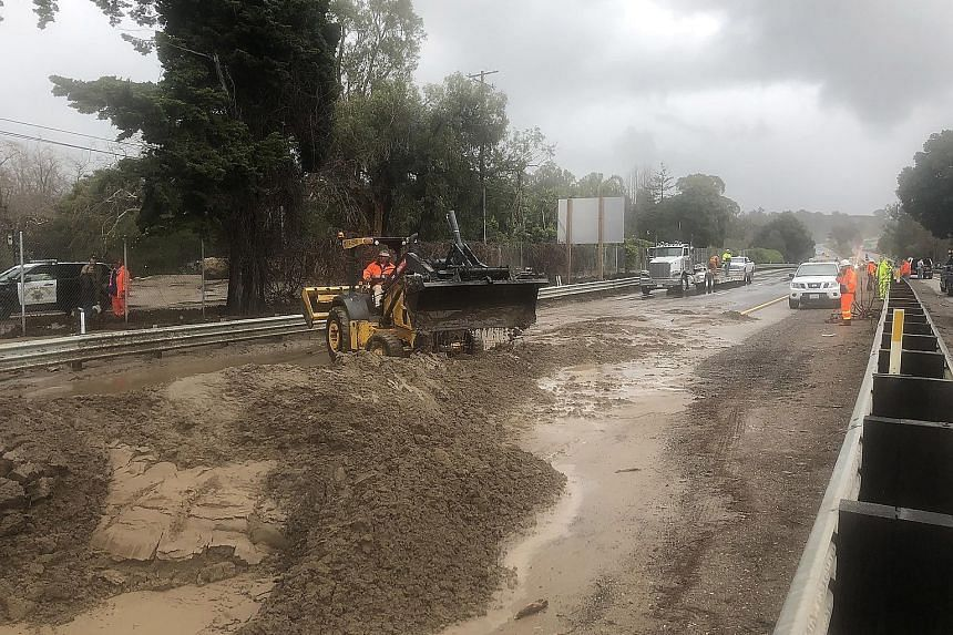 Heavy equipment being used to clear US Highway 101 of mud and water from Romero and San Ysidro creeks in Montecito, California, on Saturday. Heavy rains during the night caused road flooding and numerous trees to fall.