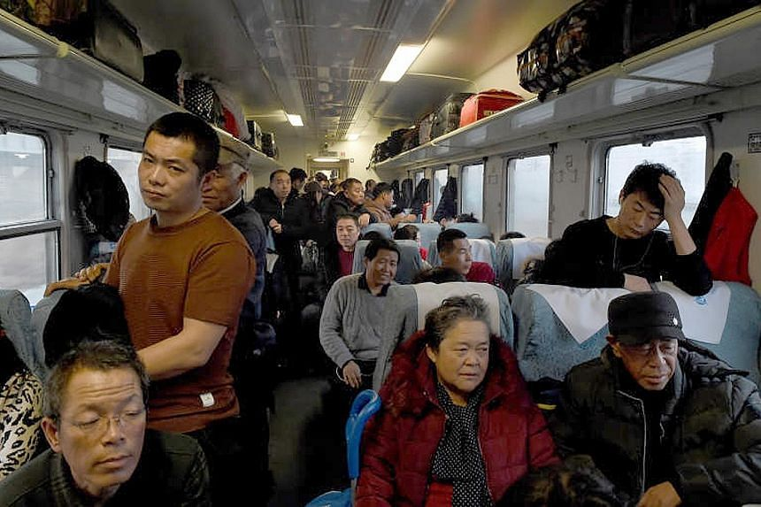 """Train master Luo Jiangjun briefing two young passengers on safety precautions aboard a """"green train"""" between Chengdu and Chongqing last Thursday."""