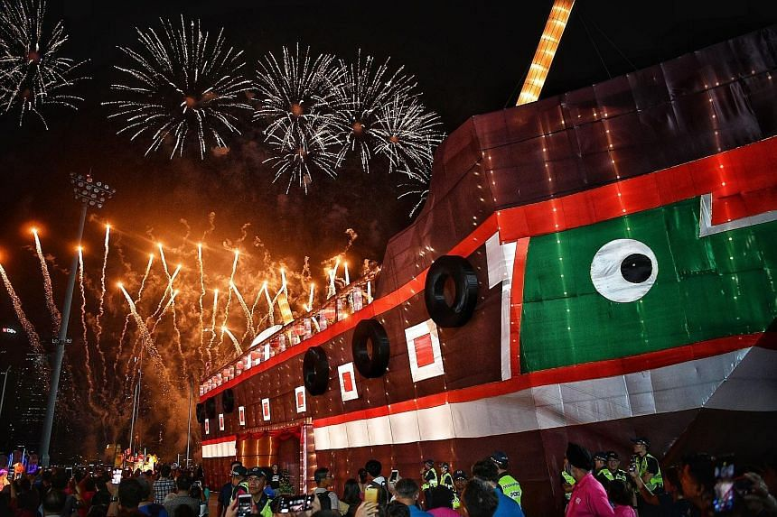 """Visitors enjoying the fireworks display at the launch of River Hongbao 2019 last night. The giant junk boat replica houses an exhibition, """"A Harbour And Home: The Singapore River Through Time"""", which highlights the Singapore River's transformation ov"""