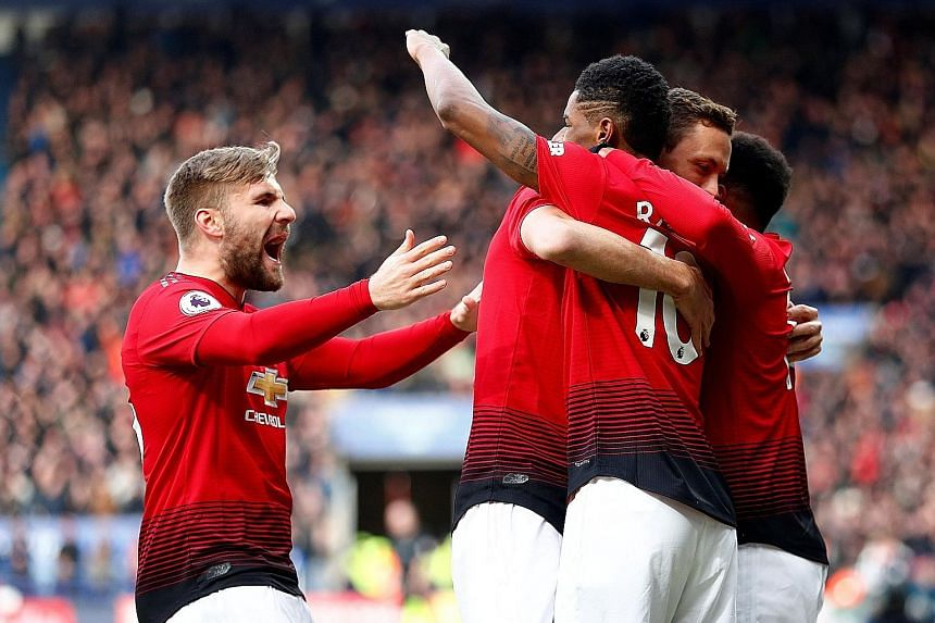 Manchester United forward Marcus Rashford (No. 10) celebrating scoring his goal with Luke Shaw and other teammates yesterday as the Red Devils beat Leicester 1-0 to keep their hopes of a top-four finish alive. Below: The striker opened the scoring in