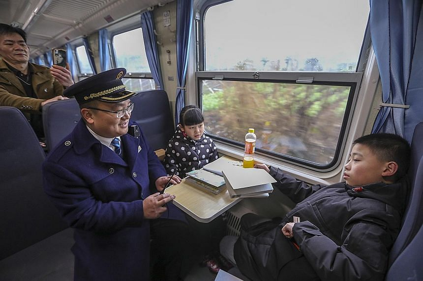 """Migrant workers on a """"green train"""" service returning home to Jiagedaqi in north-eastern Heilongjiang province from Beijing last month for Chinese New Year."""