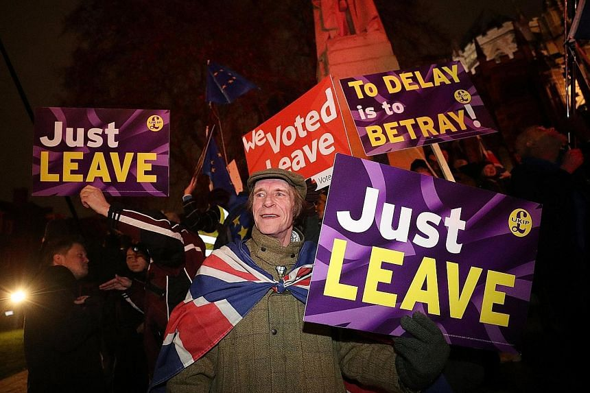 Pro-Brexit demonstrators outside Britain's Parliament in London last Tuesday. On March 29, unless something is done, Britain will fall out of the European Union without a deal. That will affect every aspect of the economy, says the writer.