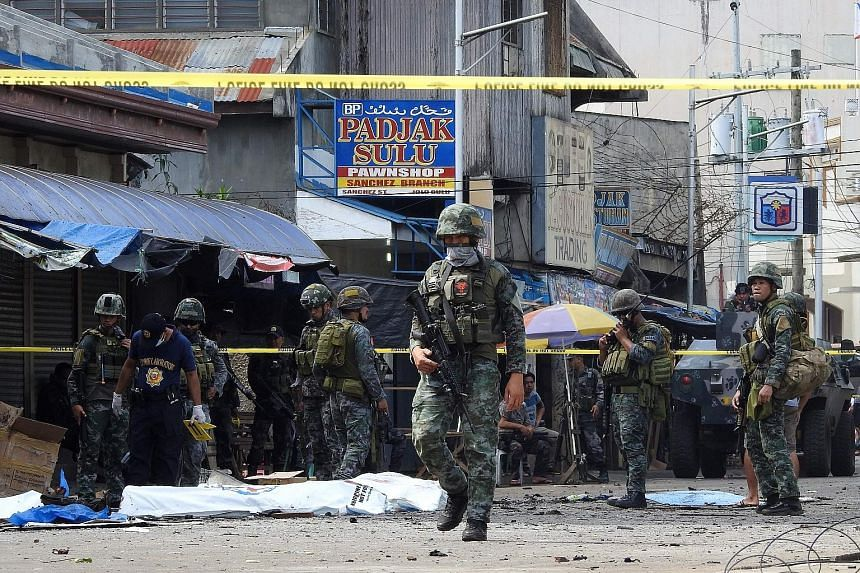 Soldiers keeping watch as investigators marked out evidence near body bags after blasts at a church in Jolo, Sulu province, on Mindanao island, recently. The leader of the Ajang-ajang faction of the Abu Sayyaf is suspected of helping to plot the atta