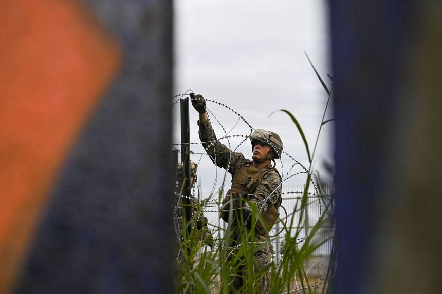 Members of the US military place concertina wire along the border fence near the California-Mexico border in November 2018.