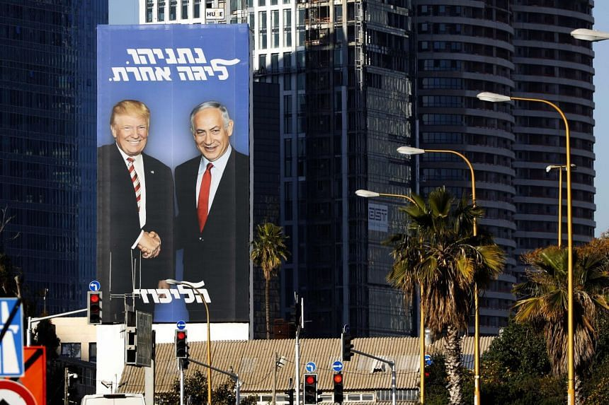 In Tel Aviv, an election billboard shows Benjamin Netanyahu and Donald Trump shaking hands.