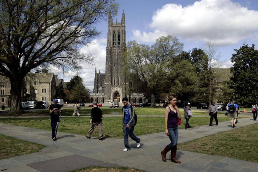 Students walk by Duke Chapel on the campus of Duke University in Durham, North Carolina.
