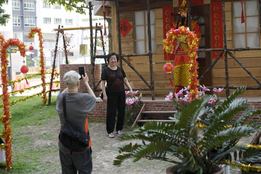 Visitors posing for pictures in front of the Chinese New Year cabin in Woodlands.