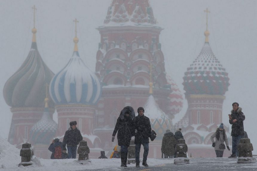 People walk in Red Square during heavy snowfall in Moscow, Jan 27, 2019.
