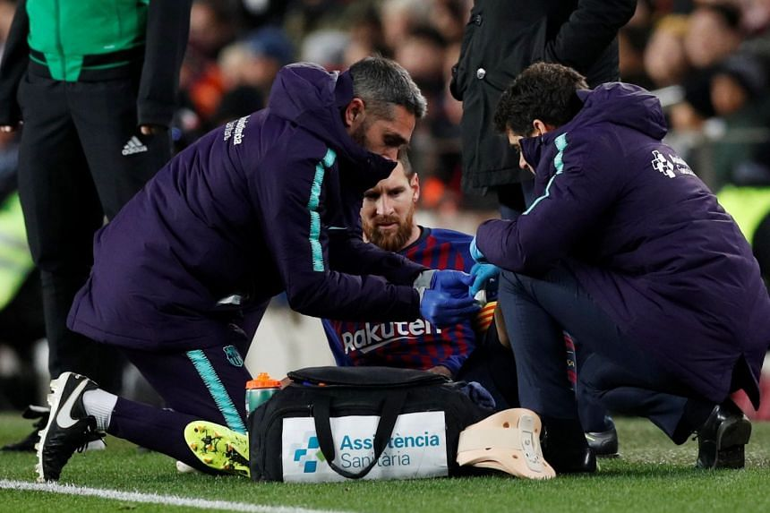 Messi receives treatment after sustaining an injury against Valencia.