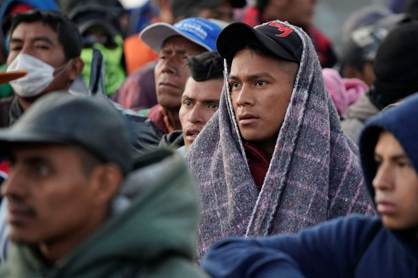 Migrants wait in line to get into buses during their journey towards the US, in Saltillo, Mexico, Feb 4, 2019.