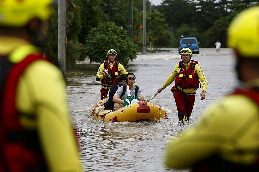 Queensland Fire and Emergency Services crew members using an inflatable boat to pull residents through floodwaters in Hermit Park, Townsville.