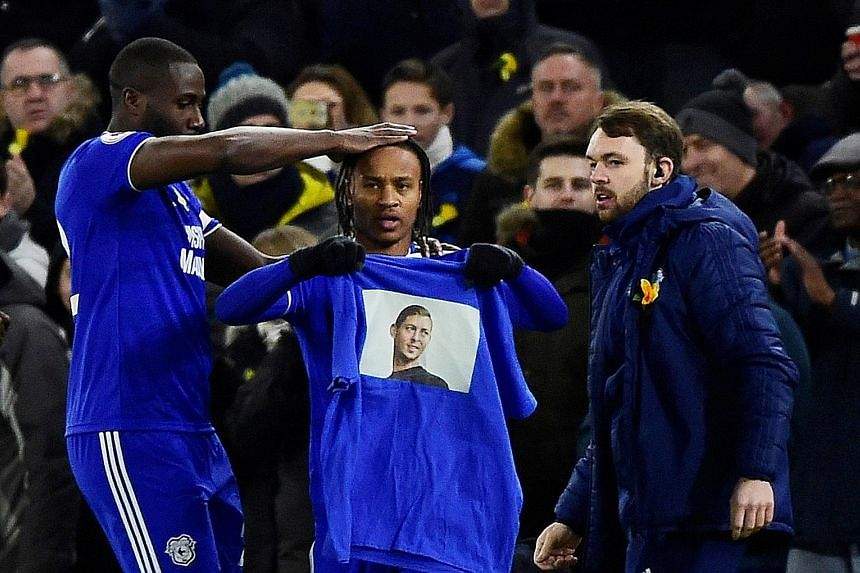 Cardiff City's Bobby Reid celebrates scoring their first goal against Bournemouth last Saturday by displaying a shirt paying tribute to Emiliano Sala.