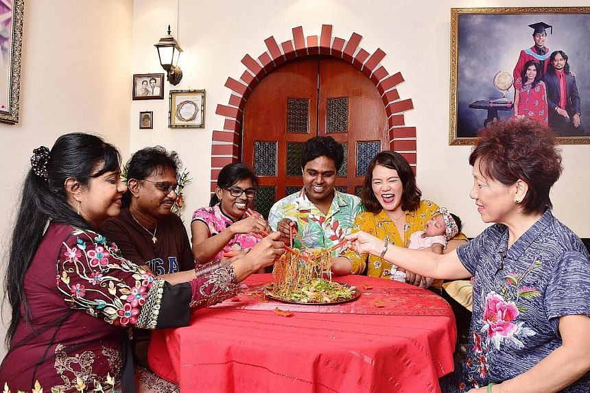 (From left) Ms Stella George, Mr Christopher George, Madam Jenet Nathan, Mr Abraham Christopher, Ms Jacqueline Lui, with eight-week-old Diana Abraham, and Madam Ellen Lim tossing yusheng during their Chinese-Indian reunion dinner.