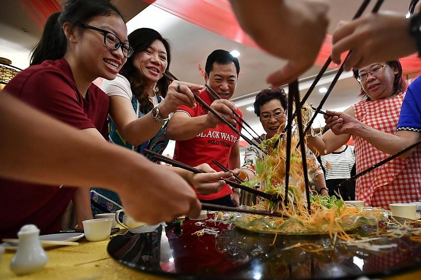 Madam Siah Choo Ing (fourth from left), 79, tossing yusheng with (from left) her granddaughter Krystal Low, 17, daughter-in-law Katharine See, 50, son Kenny Low, 51, and daughter Irene Low, 52, during their reunion lunch at Swatow Seafood restaurant