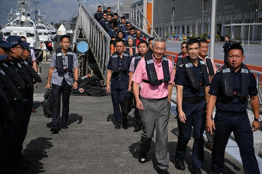 Prime Minister Lee Hsien Loong on the jetty at PCG Brani Base yesterday morning. He was accompanied by Mrs Lee and Home Affairs Minister K. Shanmugam.