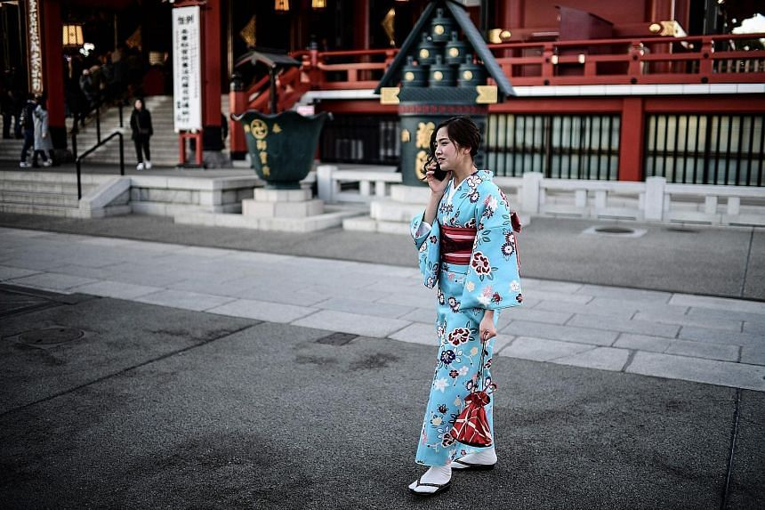 A woman using a mobile phone in Tokyo's Asakusa district. Japan's three telcos are conducting 5G mobile communications trials. A 5G service robot serving bottles of water to travellers at a Hangzhou railway station during the Spring Festival travel r