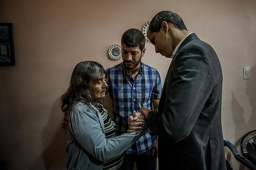 Mr Juan Guaido comforting Ms Ana Cecilia Buitrago on Sunday. Her son, Mr Jhonny Godoy, was killed by Venezuela's security forces during a recent demonstration against the government of President Nicolas Maduro.
