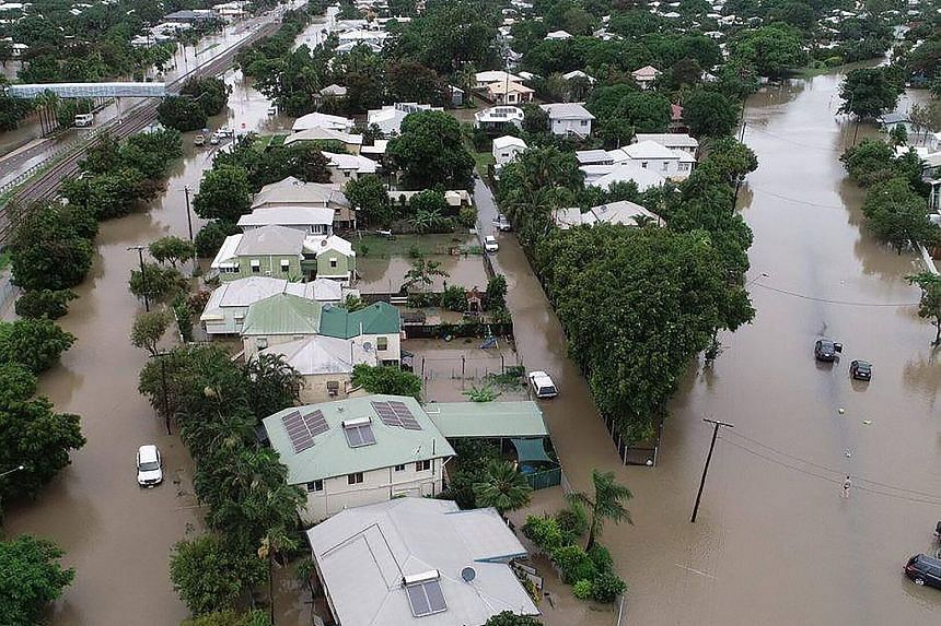 (Above) Gunner Tavis McEwan from the Royal Australian Artillery helping to evacuate a resident from her home amid the rising floodwaters in Townsville. (Left) A crocodile spotted on the streets in Townsville yesterday. A photo from the Queensland Fir