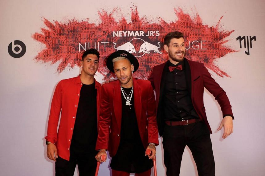 Neymar poses with Brazilian surfer Gabriel Medina (left) and a guest as he arrives at his birthday party in Paris, on Feb 4, 2019.