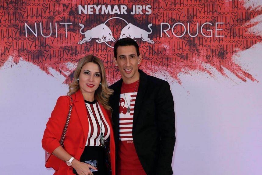 Paris Saint-Germain's Argentine midfielder Angel Di Maria (right) and guest pose as they arrive at the birthday party of Brazilian forward Neymar.