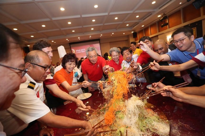 PM Lee (centre), Mrs Lee and NTUC President Mary Liew during a traditional lohei session with workers, union leaders and management staff.