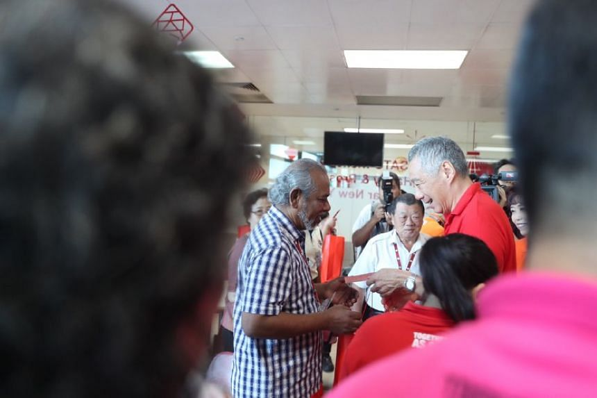 PM Lee meets a worker at ground-handling and catering firm Sats at Changi Airport, on the morning of the first day of the Chinese New Year.