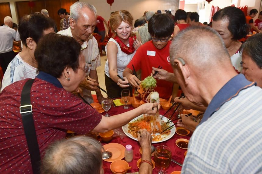 Volunteers from the American Women's Association tossing yu sheng with the elderly during a Lunar New Year's Eve reunion lunch organised by the Henderson-Dawson Citizens' Consultative Committee.