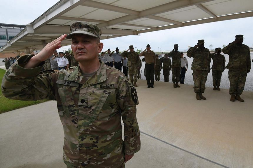 US soldiers salute during a grand opening ceremony of the new headquarters building for the United Nations Command and US Forces Korea at Camp Humphreys in Pyeongtaek, on June 29, 2018.