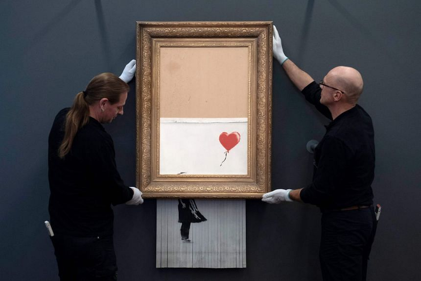 """Employees hang up the artwork """"Love is in the Bin"""" by British street artist Banksy at the Frieder Burda Museum."""