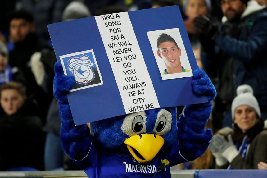 Cardiff City mascot Bartley Bluebird displays a banner paying tribute to Emiliano Sala.