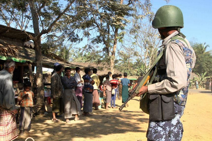 A Myanmar border guard policeman stands near a group of Rohingya Muslims in front of their homes in the Buthidaung township in the restive Rakhine state of Myanmar, on Jan 25, 2019.