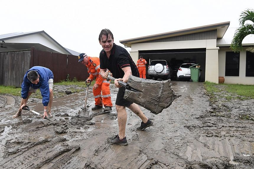 Residents clearing mud off their driveway in Hermit Park, Townsville, in Queensland after days of torrential rain caused massive floods.
