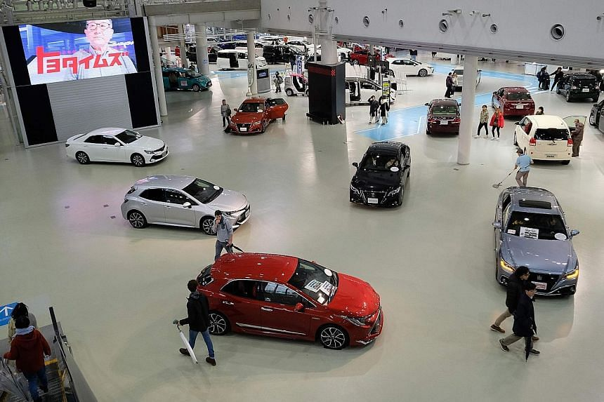 A Toyota car showroom in Tokyo yesterday. The Japanese car giant's net profit for the nine months to December came to 1.42 trillion yen, down 29.3 per cent from the same period the previous year. It now expects annual net profit of 1.87 trillion yen