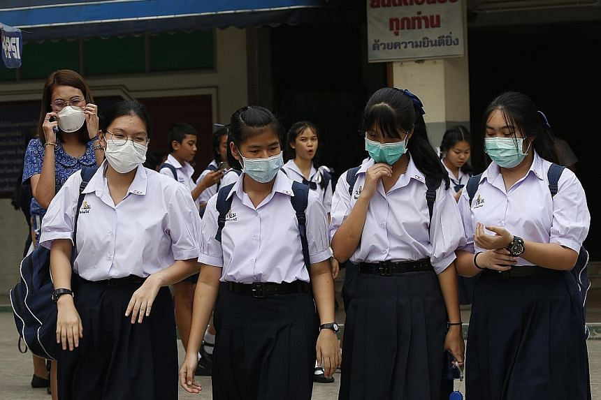 Students wearing masks as heavy air pollution continues to affect Bangkok. A rattled Thai government is stepping up oversight of factories.