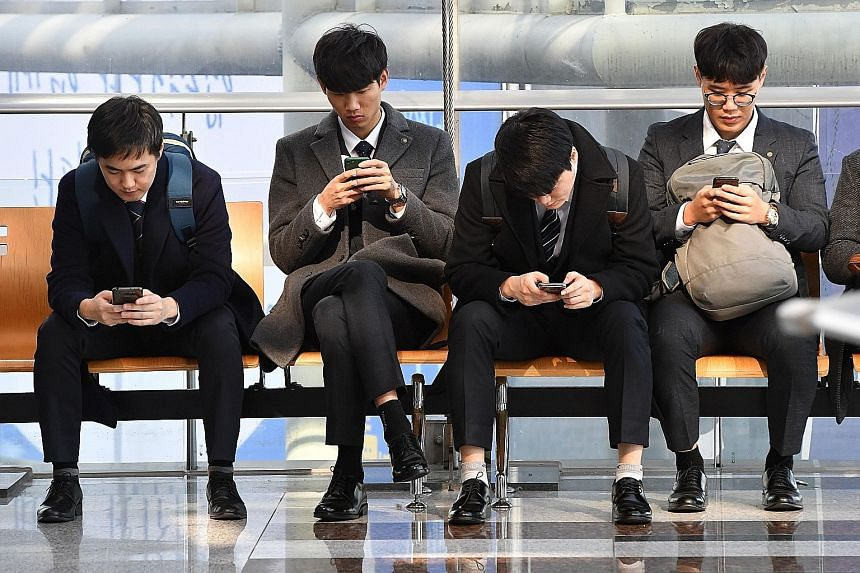South Koreans checking their smartphones. A Pew Research Centre report has found strong majorities of adults using smartphones in the world's wealthier countries, led by a 95 per cent adoption rate in South Korea.