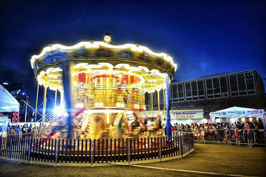 Children from underprivileged families enjoy a swirling ride on what is believed to be the first double-storey carousel in Singapore at the annual River Hongbao festival. Games and ride provider JKids Amusement sponsored $30,000 worth of games cards