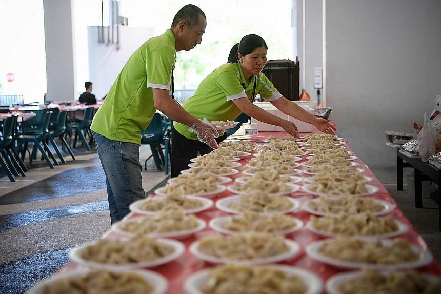 Chinese migrant worker Wang Yong (left) and fellow Chinese national Dai Yan Zhao, 47, preparing to serve traditional dumplings for over 150 attendees at a Chinese New Year party yesterday.