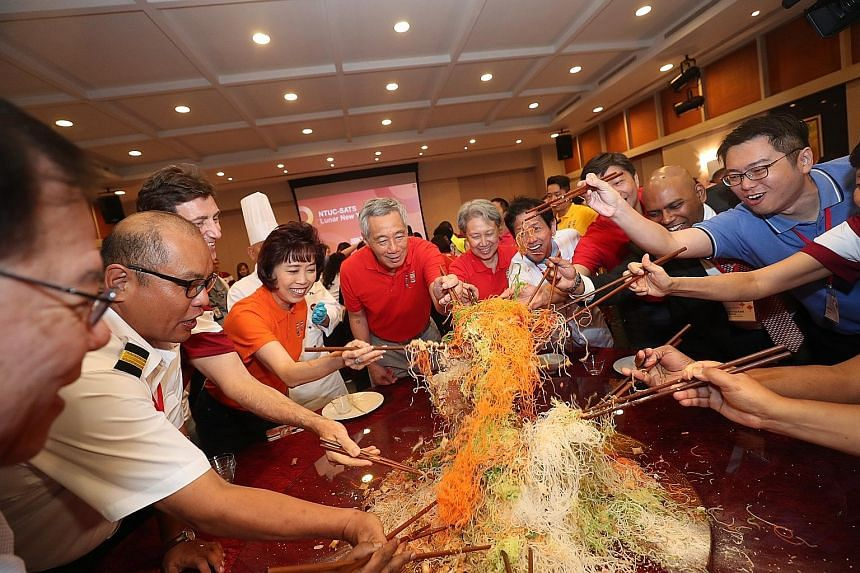 Prime Minister Lee Hsien Loong, Mrs Lee and NTUC president Mary Liew (in orange) having a lohei session with workers, union leaders and management staff at ground-handling and catering firm Sats at Changi Airport on Tuesday, the first day of the Chin